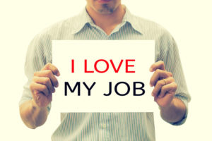 "job satisfaction image - man holding ""I love my job"" sign"